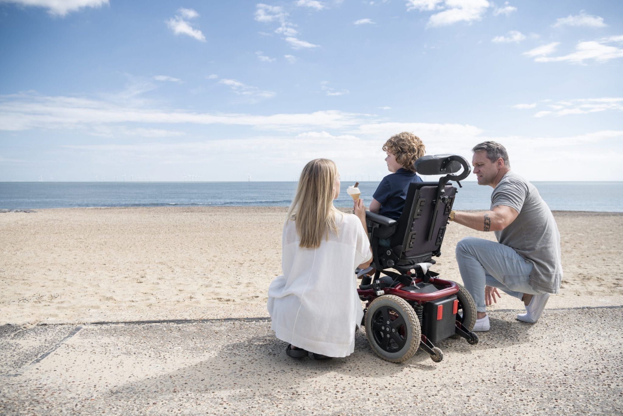 Parents-crouching-by-wheelchair-at-beach