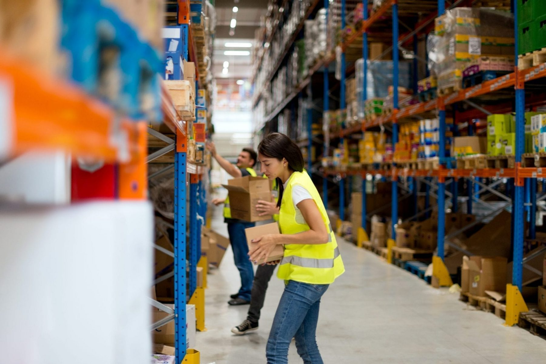 Warehouse workers are stacking goods onto the shelves