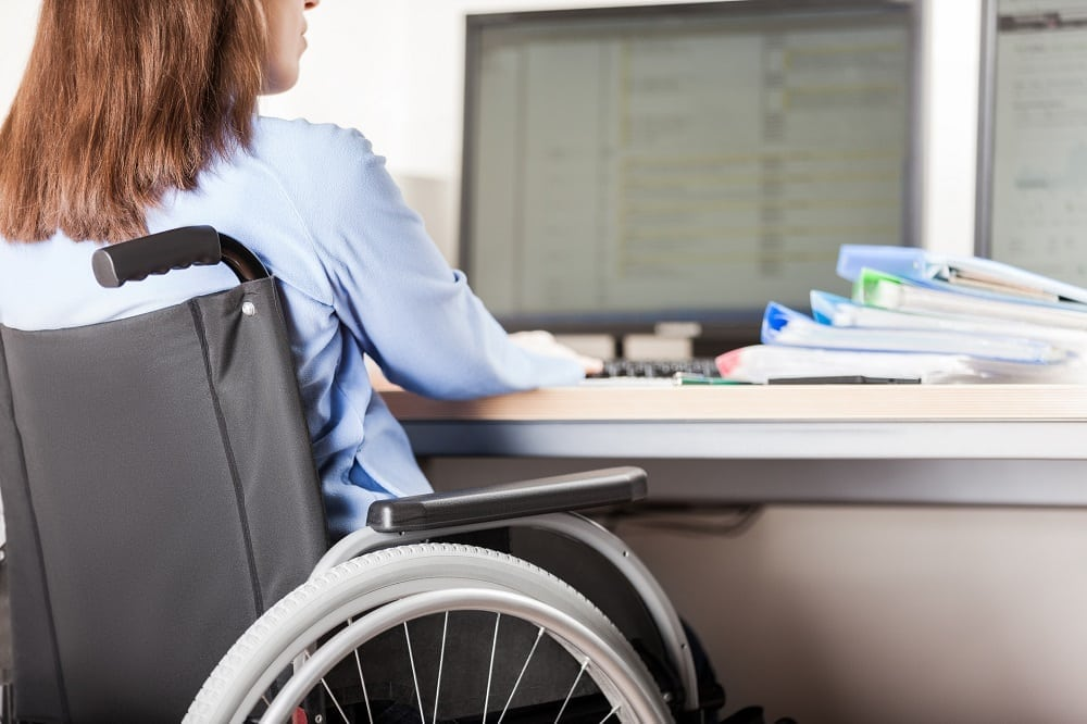 Disabled woman sitting wheelchair working office desk computer