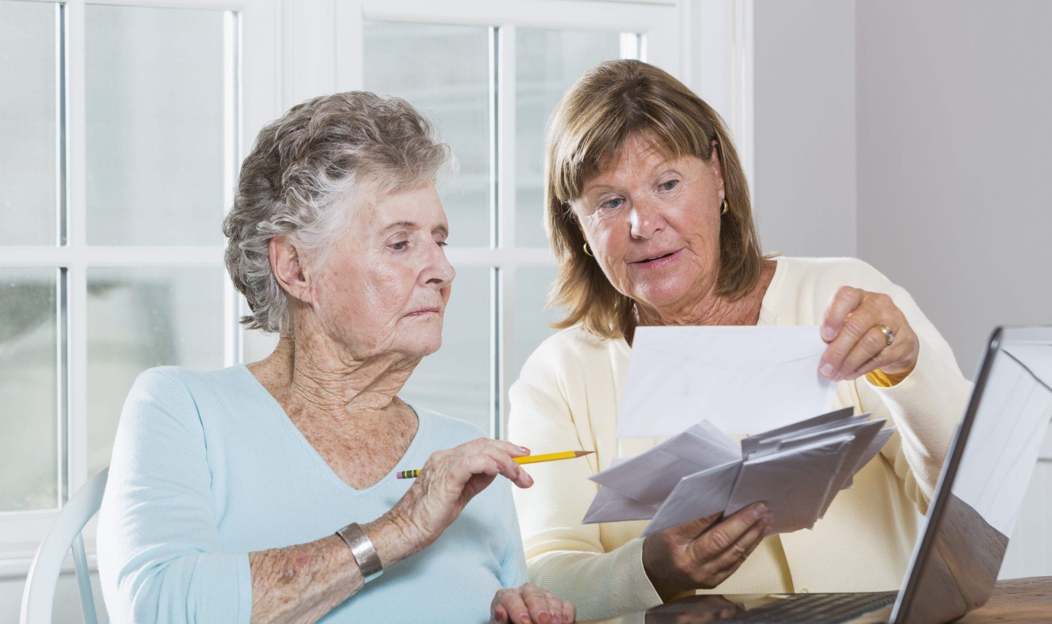 Woman helping elderly mother pay bills.