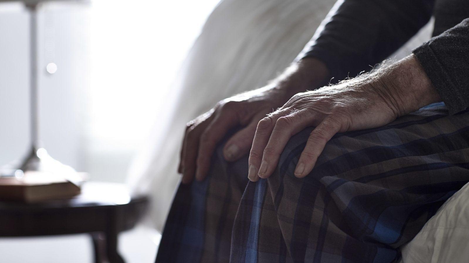 Elderly Man Sitting Bedside Stock Photo