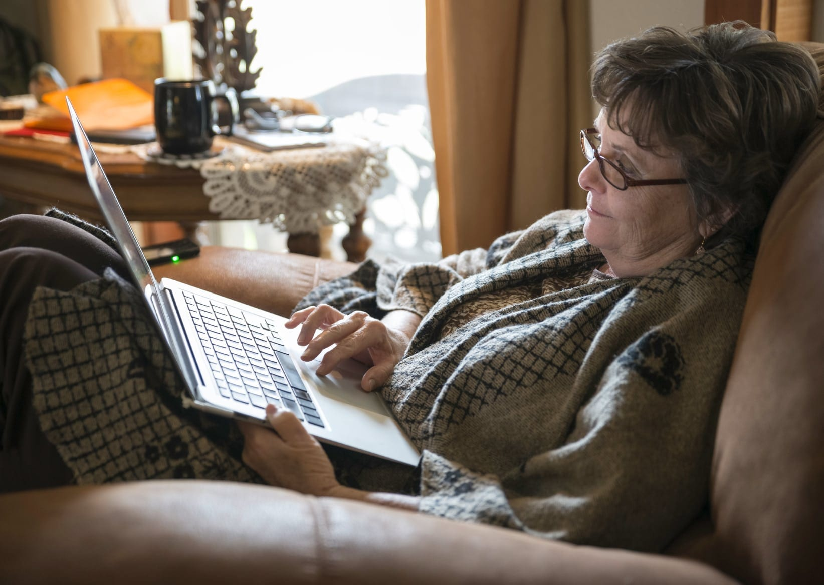 Mature Woman Using A Laptop On The Couch