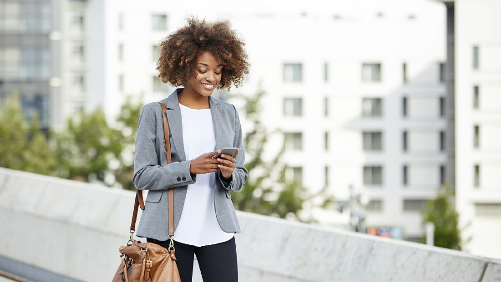 Young Woman Using Her Mobile Phone While Walking Stock Photo