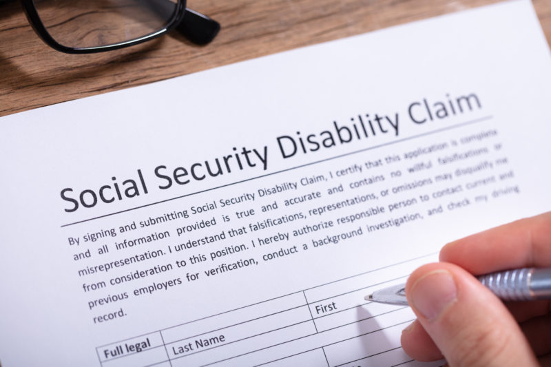 person filling out a Social Security Disability claim form