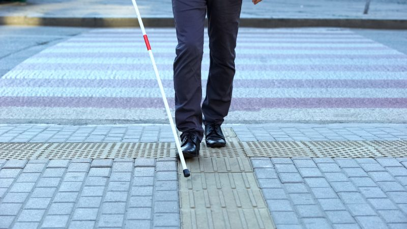 A blind man using his cane to cross the street in Los Angeles.
